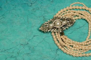 Pearl necklace and hair accessaries on green background