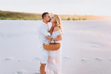A bearded man and a blond woman with a basket hug, standing on the white sand and enjoying each other. Love in the desert newlyweds. The love story of fun and love people.