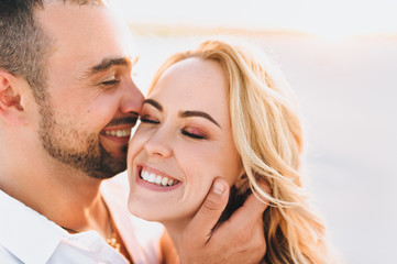 A bearded man and a blond woman are embraced and illuminated by a sunbeam. Closeup portrait of emotional people at sunset. Love in the desert newlyweds. The love story of merry and lovers young.