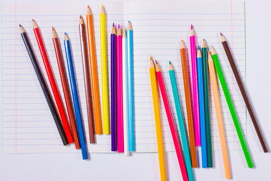 Цветные карандаши на белом листе тетради.