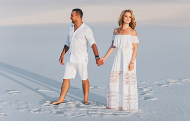 A bearded man and a blond woman walk, holding hands, on the white sand. Love in the desert newlyweds. The love story of young people.