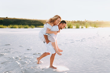 A bearded man and a blond woman run and fool around in the white sand. Love in the desert newlyweds. The love story of fun and love people.