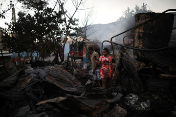 A woman takes photos with her smartphone after a fire burnt several businesses in a street of Port-au-Prince