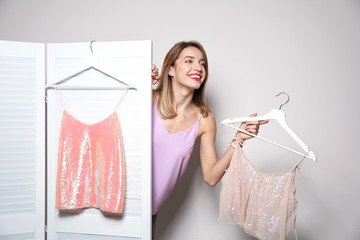 Young woman with clothes on hangers behind folding screen against light background. Dressing room