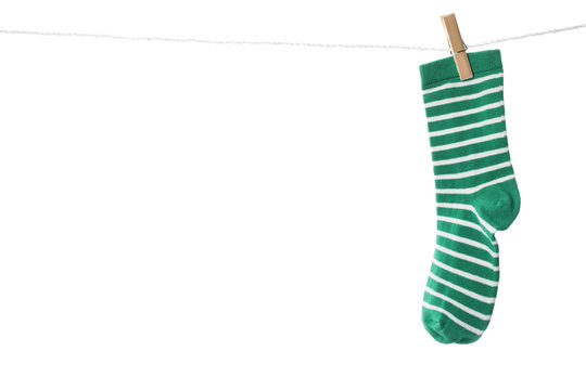 Cute child sock on laundry line against white background