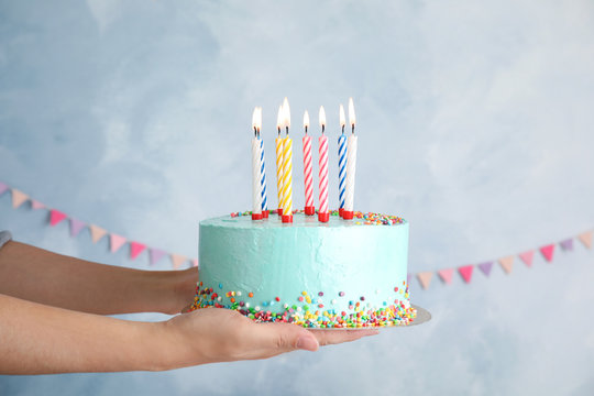 Woman holding fresh delicious birthday cake with candles on color background