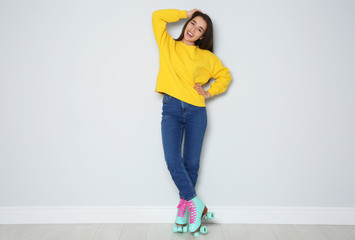 Full length portrait of young woman with roller skates near color wall