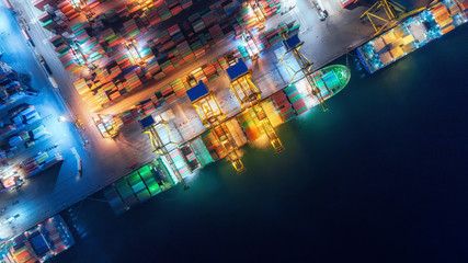 Aerial top view container ship at sea port and working crane bridge loading container for import export, shipping or transportation concept background.