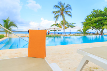 Yellow book on a sun lounger by the pool overlooking the sea. Holiday mood.