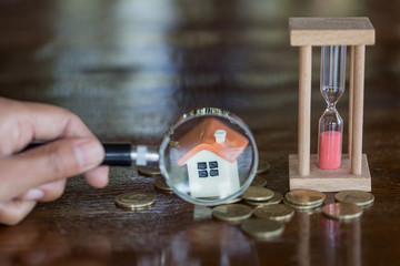 Hand hold a magnifying glass searching for a new home, Loan for real estate or save money for buy a house to family in the future concept.