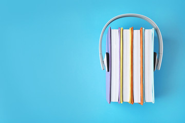 Modern headphones with hardcover books on color background, top view. Space for text