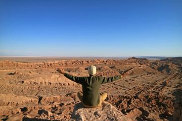A Man Sitting on the Rock Raising Arms Appreciating the Awesome view of the Moon Valley or Valle de la Luna, Atacama Desert, San Pedro Atacama, North of Chile