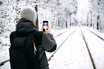 A guy with a backpack photographs on the phone the tram rails running through the snowy forest.