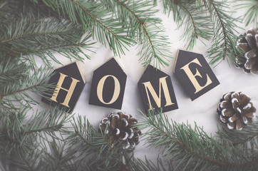 Cozy Winter Concept, Pine Branches and Home Letters on Beige Background, Top View