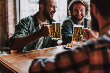 Cheerful friends toasting with drinks while spending time at pub