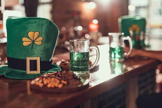 Leprechaun hat, mug of green beer and snacks on bar counter