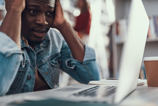 Nervous student sitting and looking at the screen of laptop