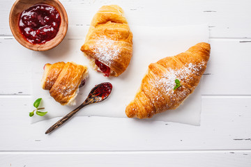 Croissants with berry jam on white wooden background.