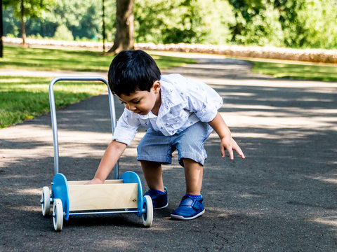 Latino child playing outside in a park with toys and trees in the background