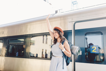 Theme transportation and travel. Portrait of young Caucasian woman with toothy smile standing at train station background with backpack waving hello while hand up, joy sign in dress and hat in summer
