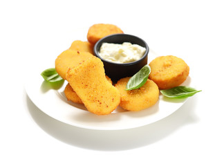 Fried chicken nuggets with white sauce and basil leaves on a white background.