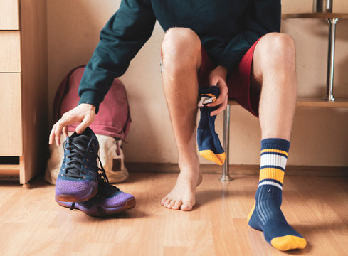 close up athlete in locker-room put on socks and wear sport clothes f
