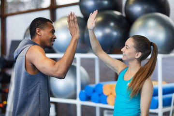 Young intercultural man and woman in activewear giving high five to each other in fitness center...