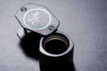 Loupe, magnifying glass on natural stone background.
