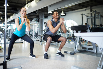 Two young intercultural athletes in activewear doing squats while training in gym or leisure center
