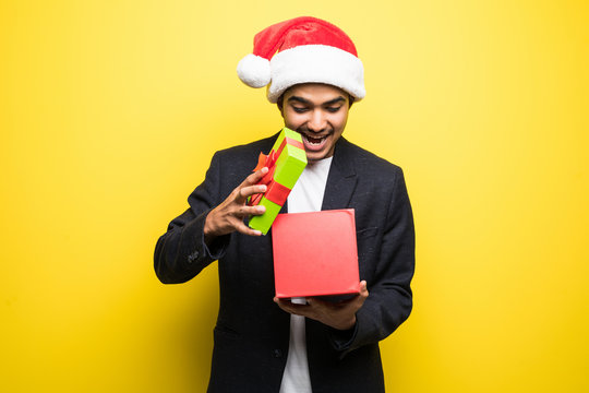 Portrait of indian young man wearing red santa claus hat, opening gift isolated on yellow background.
