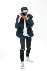 Full body length portrait Young indian man taking photo with dslr camera looking at camera isolated over white studio background.