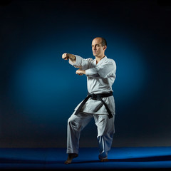 A man performs formal karate exercises on a blue tatami