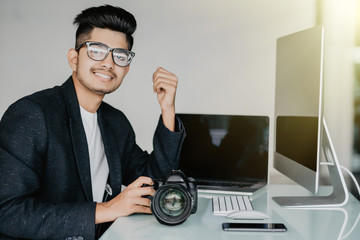 Cheerful asian reporter working in office on laptop