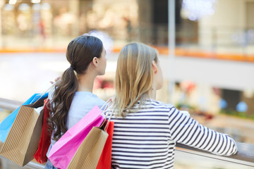 Two girls with colorful paperbags standing in large modern mall during xmas sale and looking at department on other side
