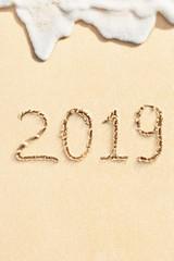 2019 written on the sandy beach