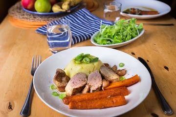 Pork tenderloin,mashed potato and carrot on plate, salad on wooden table.