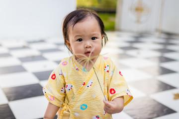Asian little girl holding flowers.