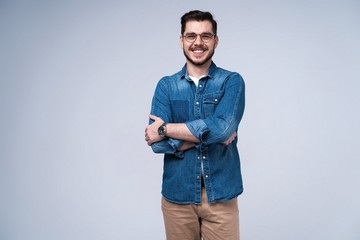 Portrait of happy fashionable handsome man in jeans shirt crossing hands and look at camera.