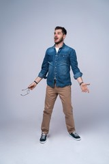 Vertical image of shocked man in shirt and jeans. Isolated on gray background.