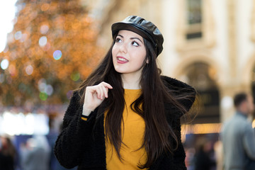 Beautiful young woman wearing a hat outdoor in a pensive expression