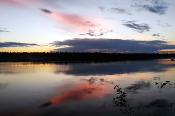 Quiet evening on the northern lake of Karelia. Beautiful sunset. Reserve Wild nature. Silence. Backdrop. Reflection of bright clouds in the water