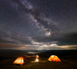 Night camping. Three illuminated orange tents in the mountains at night under starry sky, Milky way and clouds on the background of the luminous town in the valley. Between the tents lit a bonfire