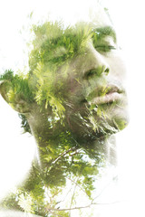 Double exposure of a young sexy man's portrait blended with branches of a tropical palm tree, showing the perfect beauty of nature's creation