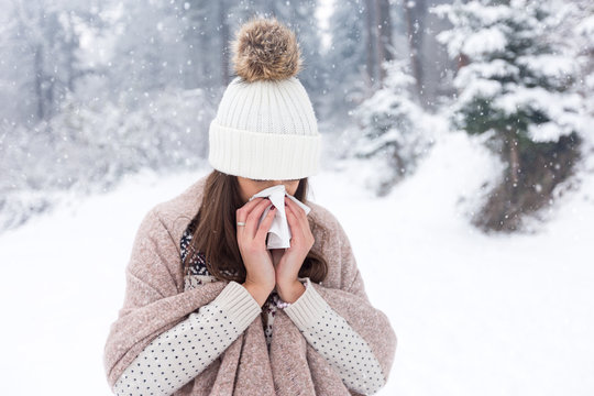 Woman uses a handkerchief at winter day