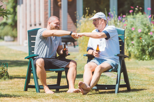 Two men drinking beer together and making power five gesture in summer sunny garden (Netherlands - Holland) - male friendship and family party concept