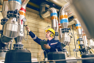 Young Caucasian worker in protective suit tightening the valve and using tablet while standing in heating plant. Wall mural