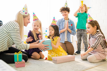 Cheerful kids opening gift box at birthday party: smiling young mother in party hat giving gift box to Asian girl while they sitting on floor in childrens room