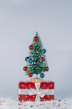 Little Christmas tree with ornaments on little gift pack with snow and shining little stars