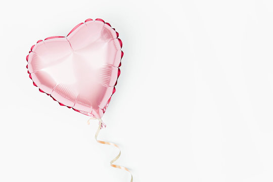 Single Balloon of heart shaped foil on white background. Love concept. Holiday celebration. Valentine's Day or wedding/bachelorette party decoration. Metallic balloon