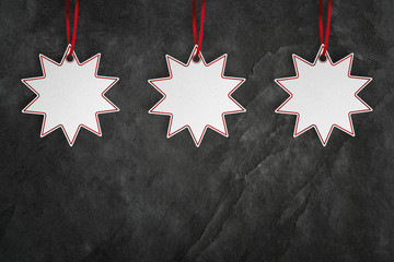 Fototapete - Three star price sticker over black slate background with copy space
